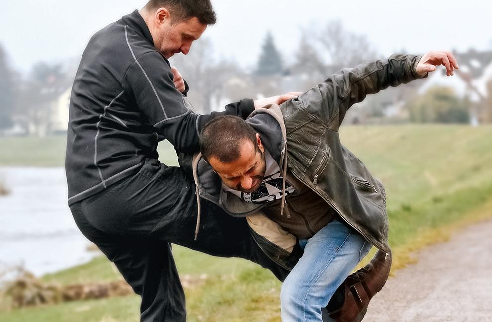 Fixierung des Angriffsarms nach einem Schlagangriff mit darauffolgendem Kick zum Genitalbereich des Angreifers