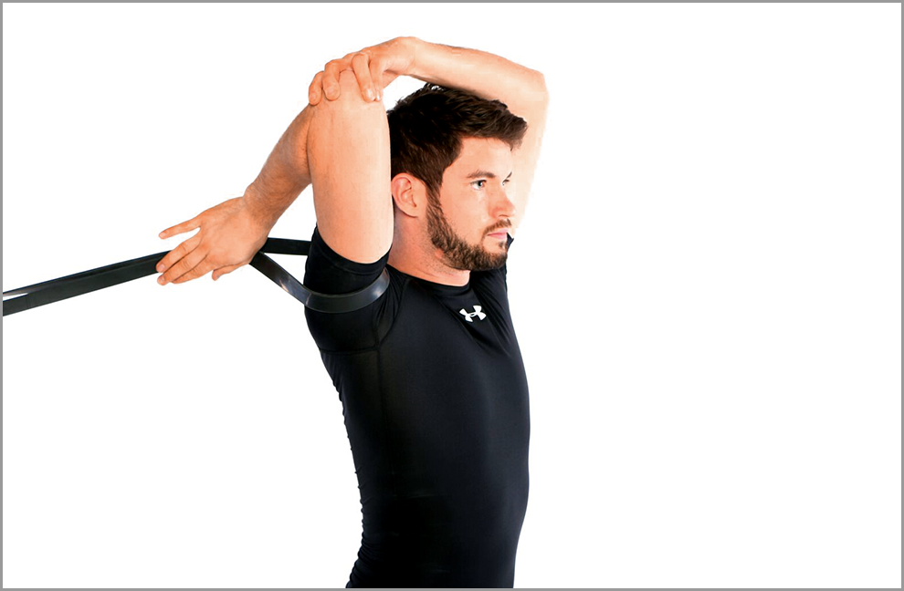 Übung 2: Schulteraußenrotation Mobilizer. Das Powerband gibt eine leichte Traktion auf die Schulter, die Hand der gleichen Seite greift in das Band. Mit der anderen Hand den Ellenbogen fixieren und eine Dehnung ausüben.